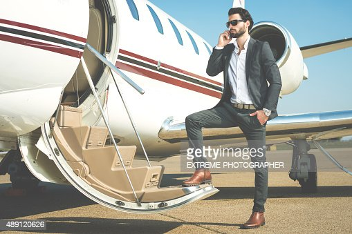Businessman with mobile phone entering the private jet