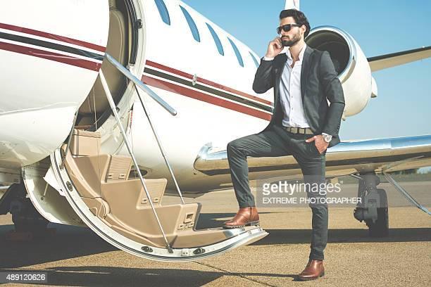Uomo d'affari con il telefono cellulare entrare nel jet privato
