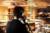 Businessman with mobile phone looking at cityscape (Digital Composite)