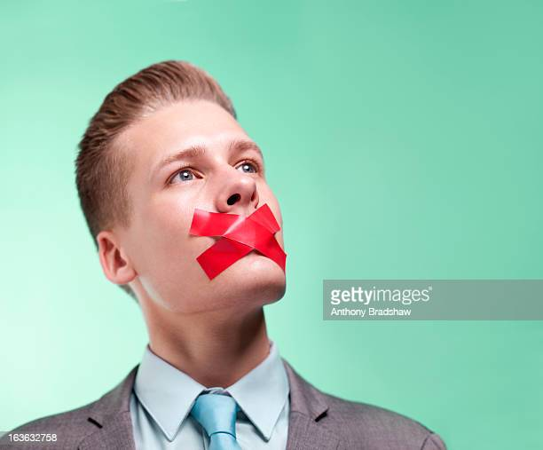 Businessman with mouth sealed closed