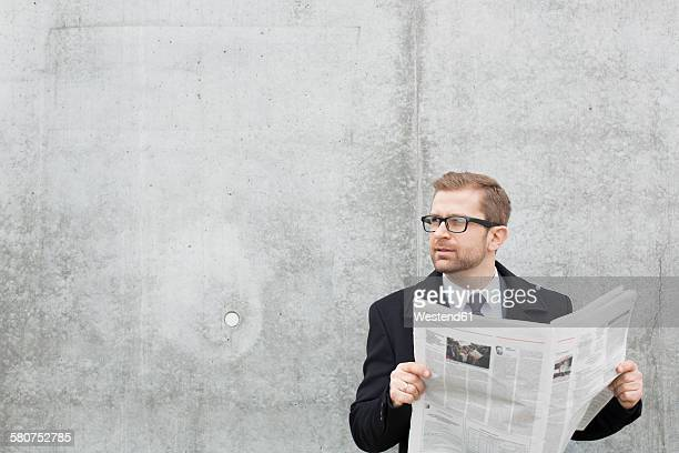 Businessman with newspaper at concrete wall