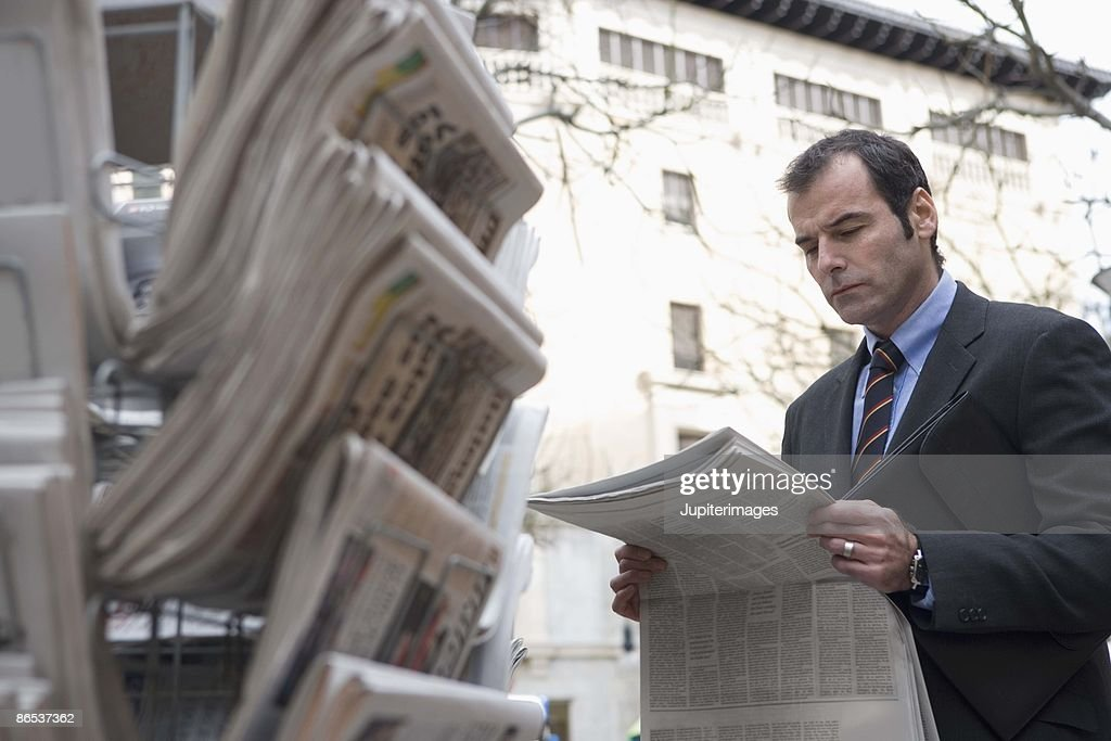 Businessman with newspaper at newsstand