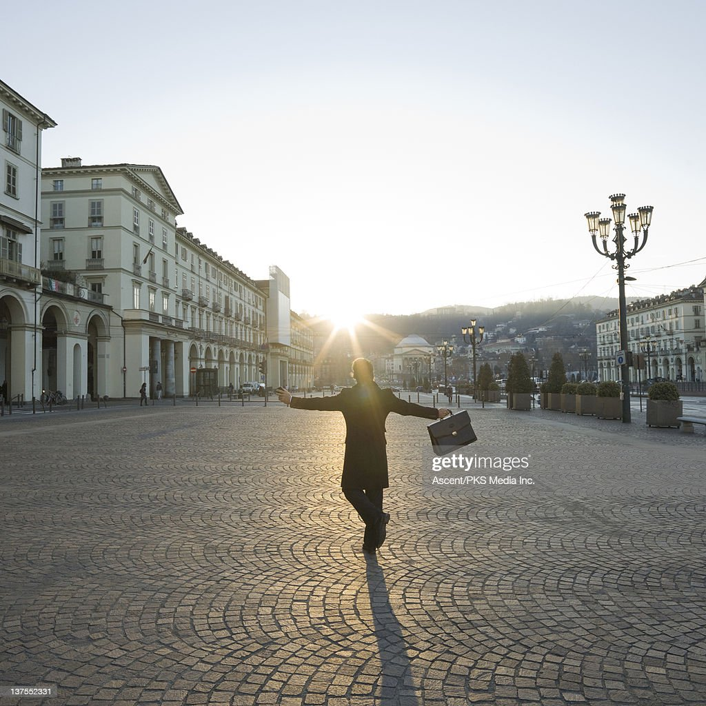 Businessman with outstretched arms in piazza : Stock Photo