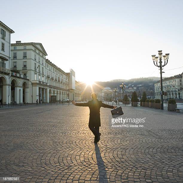 Businessman with outstretched arms in piazza