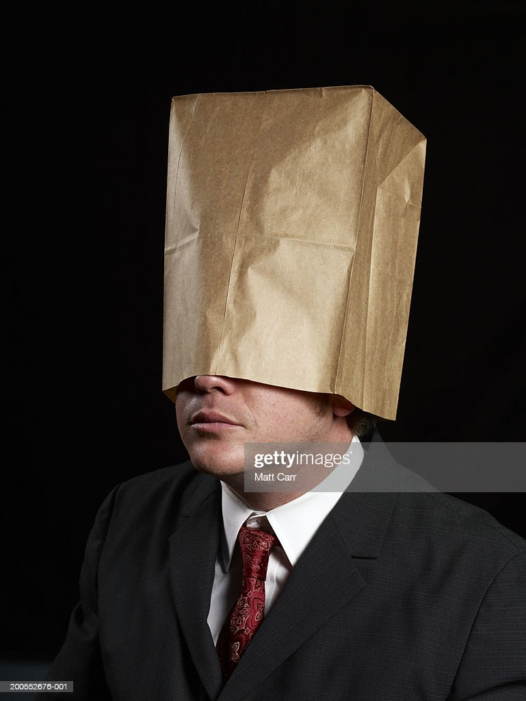 Businessman with paper bag over head : Stock Photo