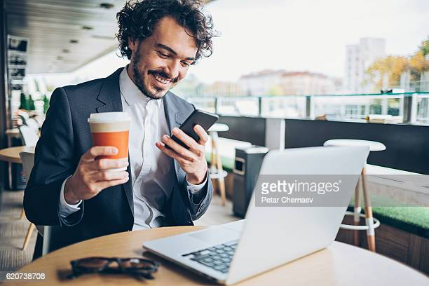 Businessman with phone and laptop in cafe