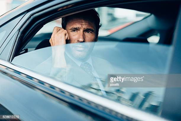 Businessman with phone inside dark car