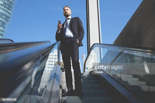 Businessman with phone standing on escalator