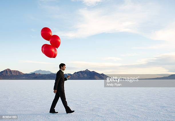 Businessman With Red Balloons Walking in Desert.