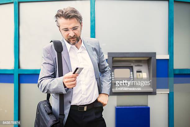 Geschäftsmann mit lehnt Kreditkarte neben Geldautomat.