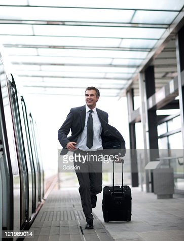 businessman with roller case, on trainstation : Stock Photo