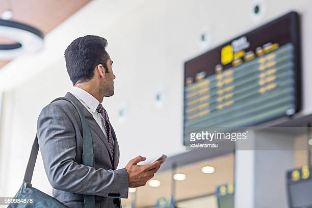 Businessman with smart phone checking arrival departure board