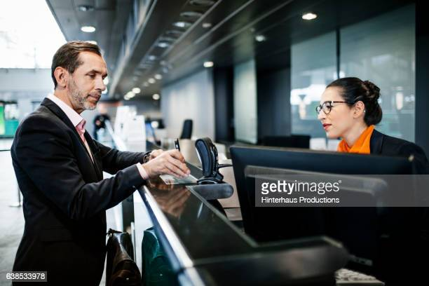 Businessman with smart phone checking mobile ticket