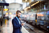 Young handsome businessman with smart phone in subway