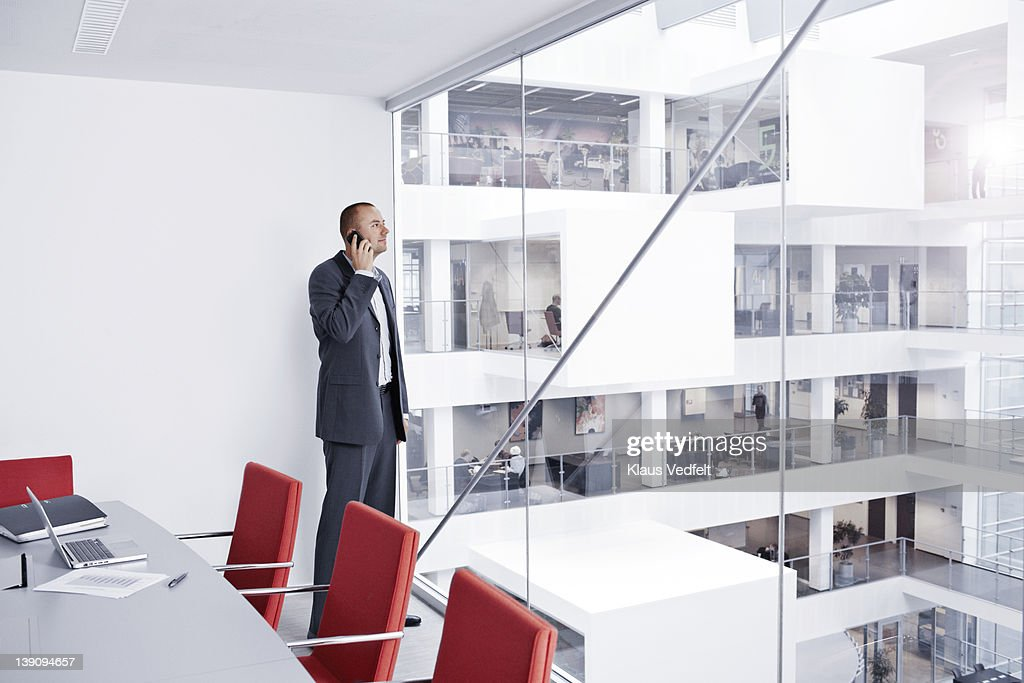 Businessman with smartphone looking out of window : Stock Photo