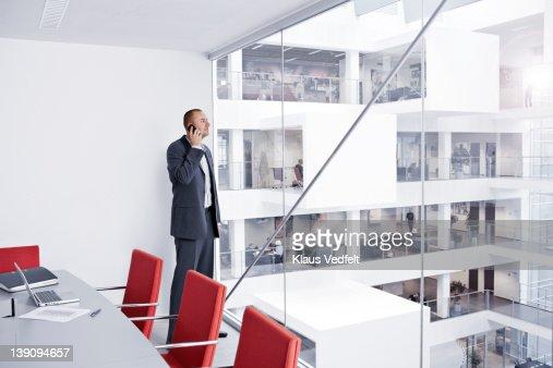 Businessman with smartphone looking out of window : Bildbanksbilder