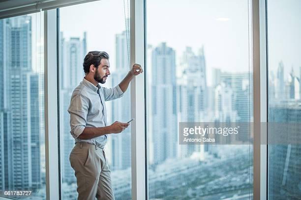 Businessman with smartphone staring through window with skyscraper view, Dubai, United Arab Emirates