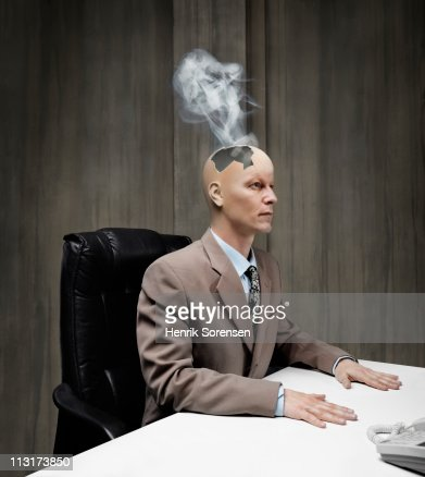 Businessman with smoke coming out of damaged head : Stock Photo