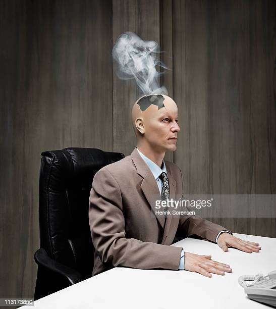 Businessman with smoke coming out of damaged head