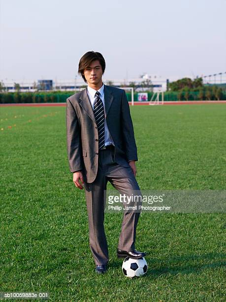 Businessman with soccer ball standing in field, portrait