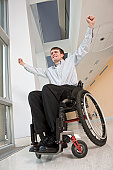 Businessman with spinal cord injury in a wheelchair looking excited