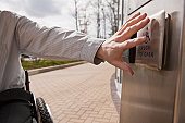 Businessman with spinal cord injury in a wheelchair pushing a button to open a door