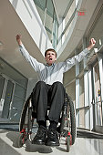 Businessman with spinal cord injury in a wheelchair with his arms raised