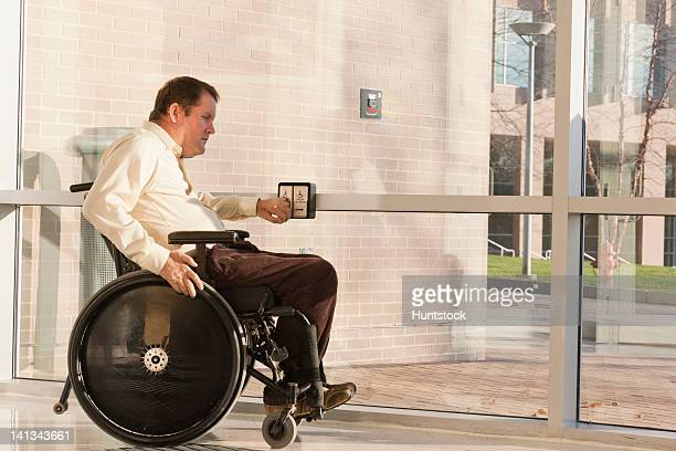 Businessman with spinal cord injury in wheelchair using automatic door opener at office building entrance