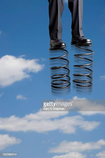 Businessman with spring shoes above clouds