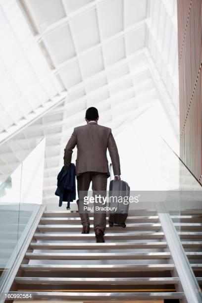 Geschäftsmann mit Koffer ascending stairs