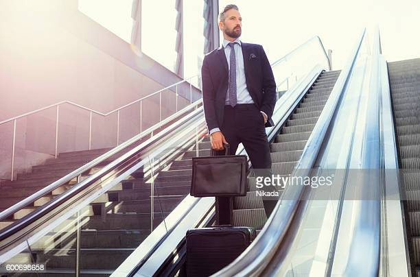 Businessman with suitcase on escalator