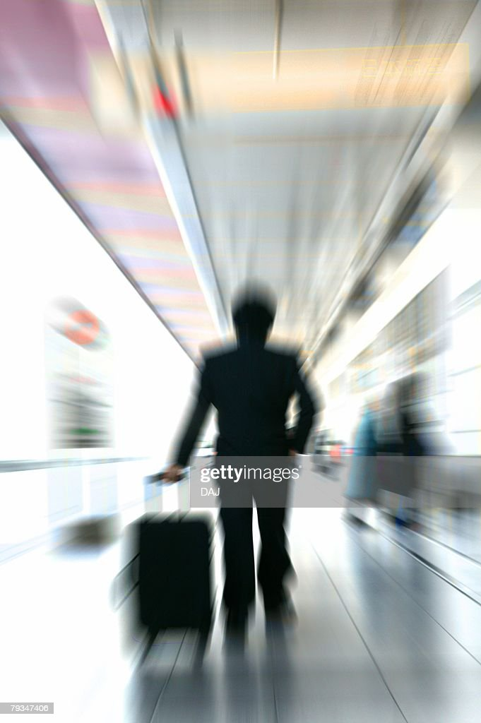 Businessman with suitcase, rear view (blurred motion) : Stock Photo