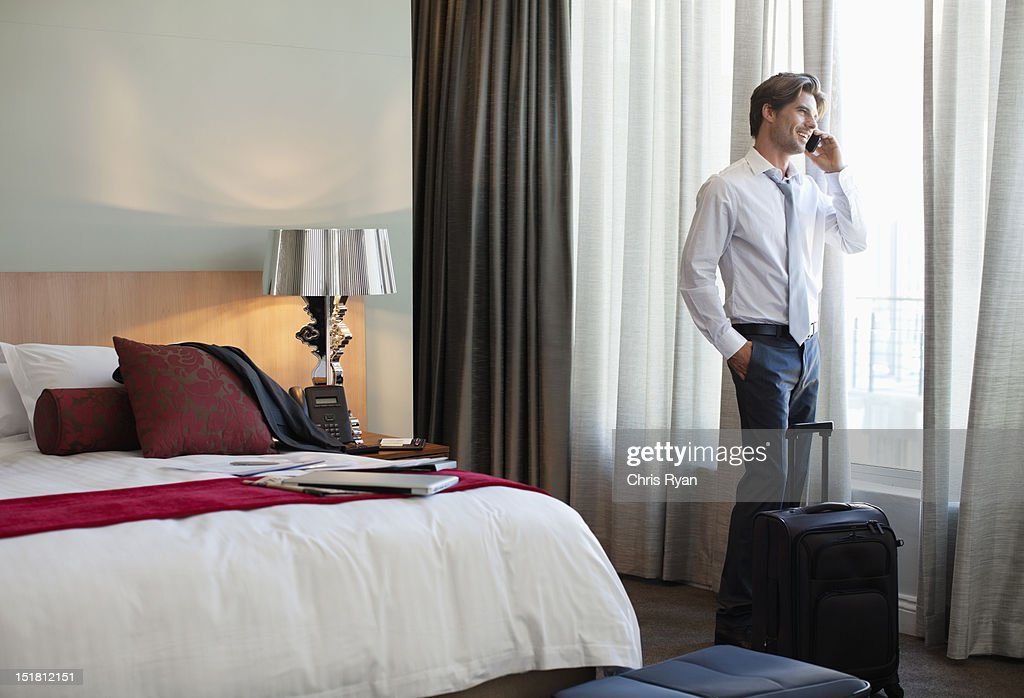 Businessman with suitcase talking on cell phone at hotel room window