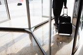 Businessman with suitcase using revolving door