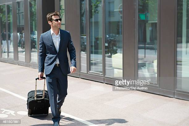 Businessman with sunglasses pulling luggage, walking in city