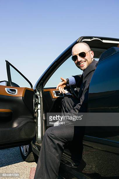 Businessman with sunglasses smiling sitting in a convertible car