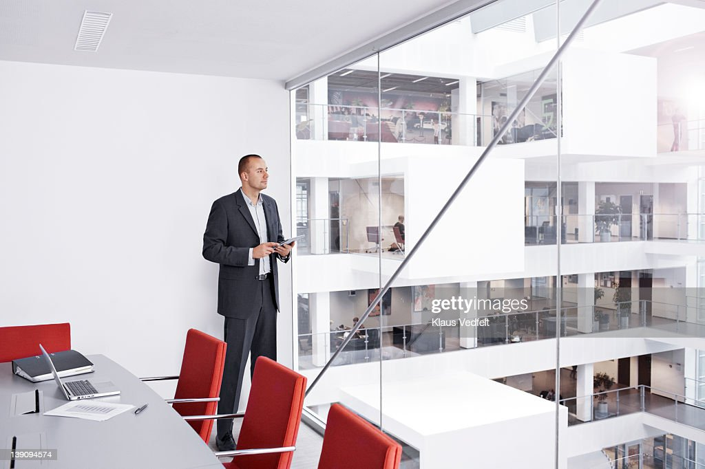 Businessman with tablet looking out of window : Stock Photo