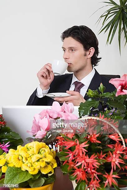 Homme d'affaires avec un thé et de plantes