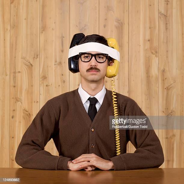 Geschäftsmann mit Telefon im Büro Gefesselt an Kopf