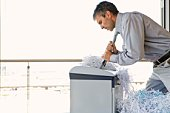 Businessman with tie in paper shredder