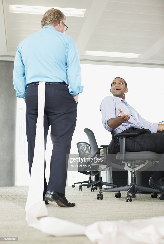 Businessman with toilet paper stuck in his pants : Stock Photo