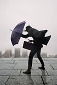 businessman with umbrella in the wind