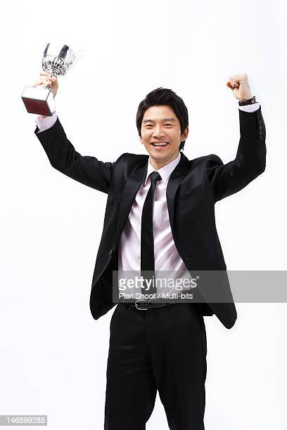 Businessman with victory trophy