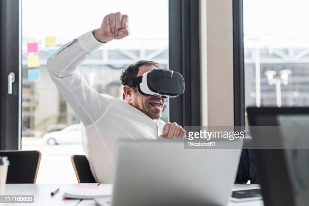 Businessman with VR glasses at desk in office