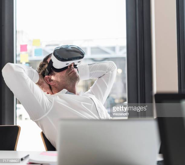 Businessman with VR glasses leaning back at desk in office