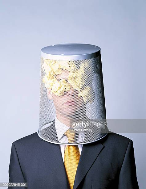 Businessman with wastepaper basket on head, portrait