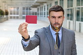 Businessman with whistle and red card.