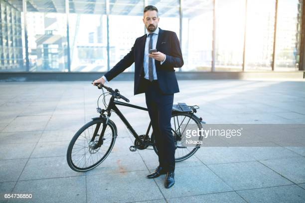 Businessman with with smart phone and bicycle