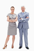 Businessman with woman who are crossing their arms against white background