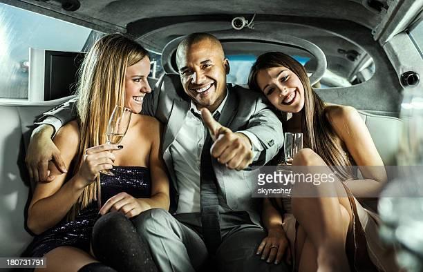 Homme d'affaires avec des jeunes femmes en limousine montrant thumbs up.